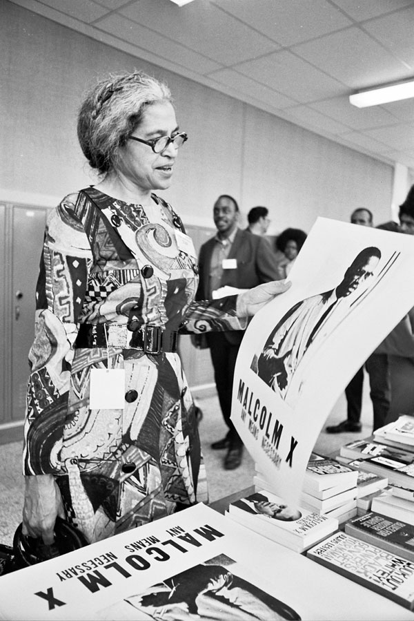 Photo of Rosa Parks admiring a poster of Malcolm X